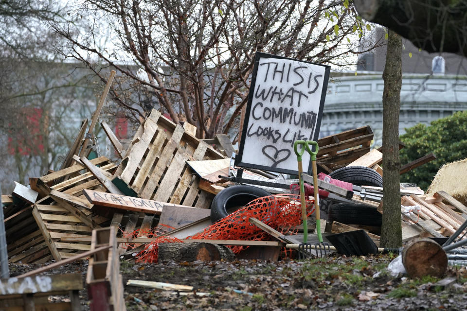 """FILE - In this Dec. 18, 2020 file photo a sign that reads """"This is what community looks like,"""" sits on top of a pile of debris and belongings at an encampment that was occupied by people lacking housing at Cal Anderson Park in Seattle. An affluent Seattle-area community has approved an ordinance prohibiting camping on public property. The city of Mercer Island says the measure will connect homeless people to shelters, but it might prove hard to enforce because of a federal court ruling. (AP Photo/Ted S. Warren,File)"""