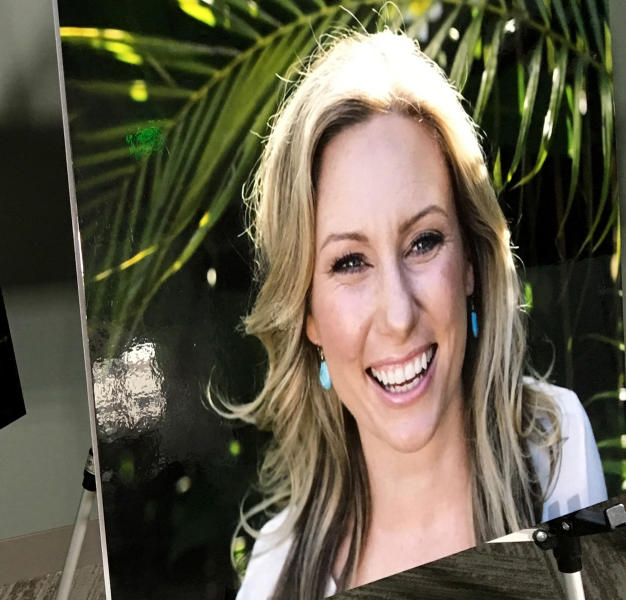 FILE - In this July 23, 2018, file photo, a poster of Justine Ruszczyk Damond is displayed at a news conference by attorneys for her family in Minneapolis. The Minneapolis woman who was fatally shot by a police officer in 2017 had spent a lifetime trying to help people and animals. Damond's relatives describe her as an animal lover who originally trained as a veterinary surgeon. (AP Photo/Amy Forliti, File)