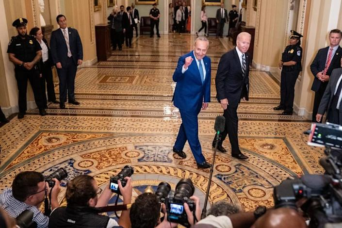 WASHINGTON, DC - JULY 14: President Joe Biden, right, and Senate Majority Leader Chuck Schumer (D-NY), left, walk together through the senate side of the U.S. Capitol Building to meet with Senate Democrats during their luncheon on Wednesday, July 14, 2021. (Kent Nishimura / Los Angeles Times)