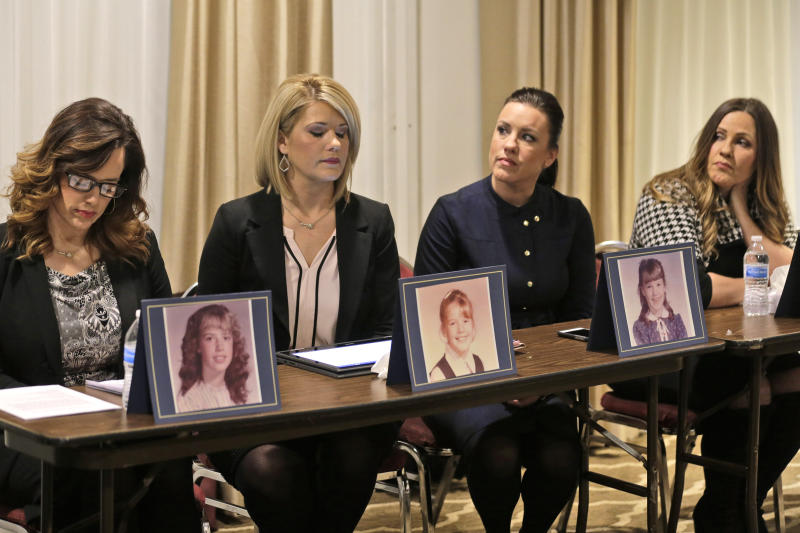 Sisters Patty Fortney-Julius, Lara Fortney McKeever, second from left, Teresa Forteny-Miller, second from right, and Carolyn Fortney sit behind pictures of themselves as children as they listen to an attorney speak to reporters during a news conference in Newark, N.J., Monday, Dec. 2, 2019. Two of the sisters from Pennsylvania, Patty and Lara, are suing the Archdiocese of Newark and the Diocese of Harrisburg, Pennsylvania. They allege clergy in Newark knew a priest had sexually abused children before he moved to Harrisburg and abused them and their sisters for years. Lawsuits alleging sexual abuse by Roman Catholic clergy are taking center stage in New Jersey as the state's relaxation of statute of limitations rules takes effect. (AP Photo/Seth Wenig)