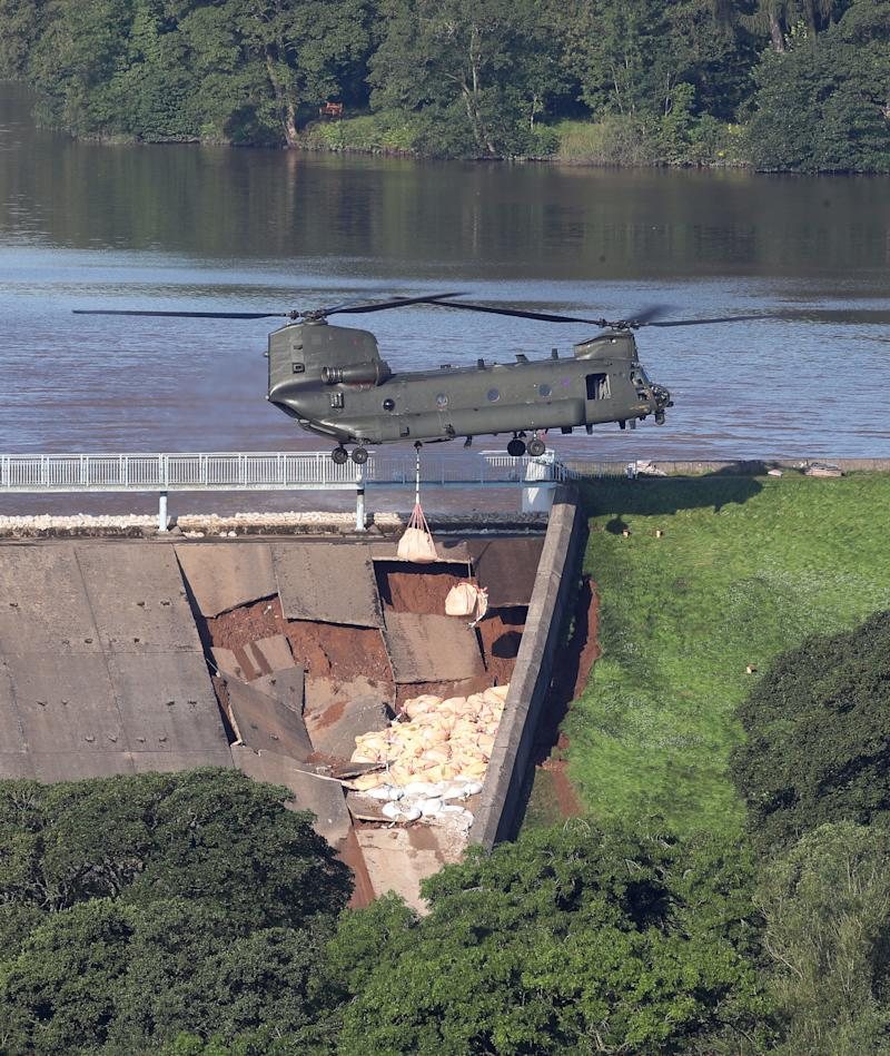 An RAF Chinook helicopter flies in sandbags to help repair the dam at Toddbrook reservoir near the village of Whaley Bridge in Derbyshire after it was damaged by heavy rainfall. PRESS ASSOCIATION Photo. Picture date: Friday August 2, 2019. See PA story WEATHER Rain. Photo credit should read: Danny Lawson/PA Wire