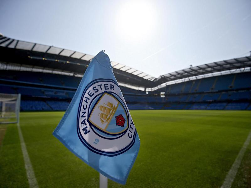The corner flag is backdropped by a general view of the Etihad stadium: EPA