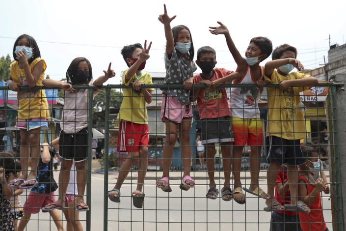 """Children flash the """"L"""" sign meaning """"Fight!"""" during a motorcade before the burial of former Philippine President Benigno Aquino III in Quezon City, Philippines on Saturday, June 26, 2021. Aquino was buried in austere state rites during the pandemic Saturday with many remembering him for standing up to China over territorial disputes, striking a peace deal with Muslim guerrillas and defending democracy in a Southeast Asian nation where his parents helped topple a dictator. He was 61. (AP Photo/Basilio Sepe)"""