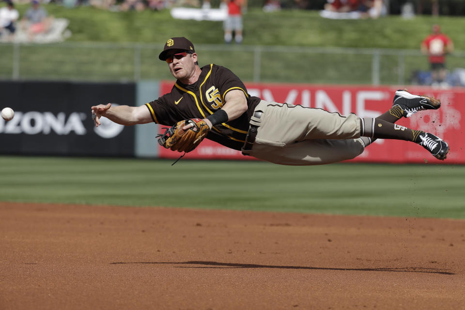 FILE - San Diego Padres' Gordon Beckham makes a throw on a ball hit by Los Angeles Angels' Mike Trout during the first inning of a spring training baseball game in Tempe, Ariz., in this Thursday, Feb. 27, 2020, file photo. The Cactus League and Arizona community leaders have asked Major League Baseball to delay the start of spring training due to coronavirus concerns just over three weeks before pitchers and catchers are supposed to report. The Cactus League made the request in a letter to Baseball Commissioner Rob Manfred obtained by The Associated Press on Monday, Jan. 25, 2021. (AP Photo/Darron Cummings, File)