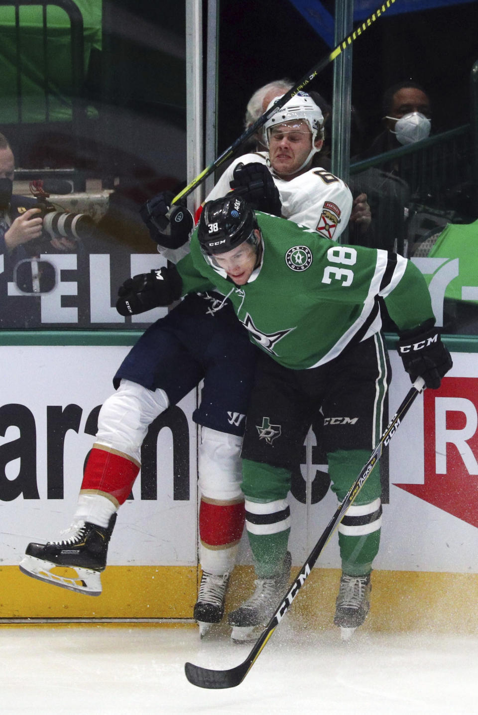 Florida Panthers defenseman Riley Stillman (61) gets checked into the boards by Dallas Stars center Joel L'Esperance (38) in the first period of an NHL hockey game on Sunday, March 28, 2021, in Dallas. (AP Photo/Richard W. Rodriguez)