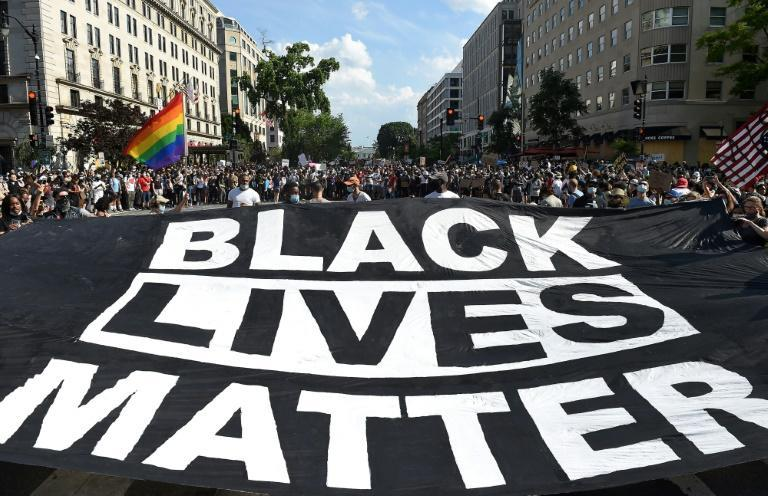 "Protesters carry a ""Black Lives Matter"" banner near the White House in June 2020"