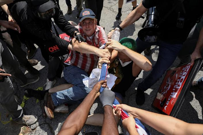 "<div class=""inline-image__caption""><p>People tussle over a Confederate flag.</p></div> <div class=""inline-image__credit"">Dustin Chambers/Reuters</div>"