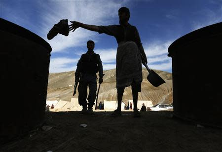 An Afghan man cooks food for displaced families near the landslide site in Argo district in Badakhshan province
