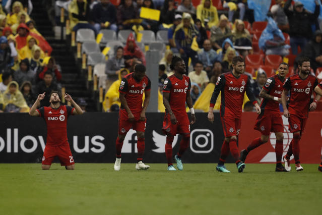 Jonathan Osorio of Canada's Toronto FC, left, celebrates after scoring against Mexico's America, during the second leg of a CONCACAF Champions League soccer semifinal in Mexico City, Tuesday, April 10, 2018. (AP Photo/Eduardo Verdugo)