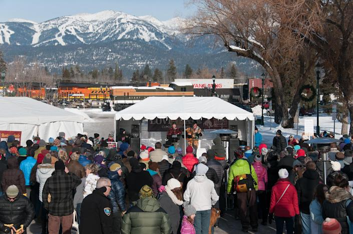 """Musician Jack Gladstone on the stage at the """"Love Not Hate"""" gathering in Whitefish, Mont., with Whitefish Mountain ski resort in the distance. (Photo: Lauren Grabelle)"""