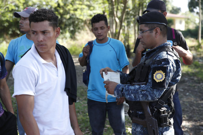 Honduras migrants trying to reach the United States show their ID card to a Guatemalan National Police agent after crossing the Honduran border, in Morales, Guatemala, Wednesday, Jan. 15, 2020. Hundreds of mainly Honduran migrants started walking and hitching rides Wednesday from the city of San Pedro Sula and crossed the Guatemala border in a bid to form the kind of migrant caravan that reached the U.S. border in 2018. (AP Photo/Moises Castillo)