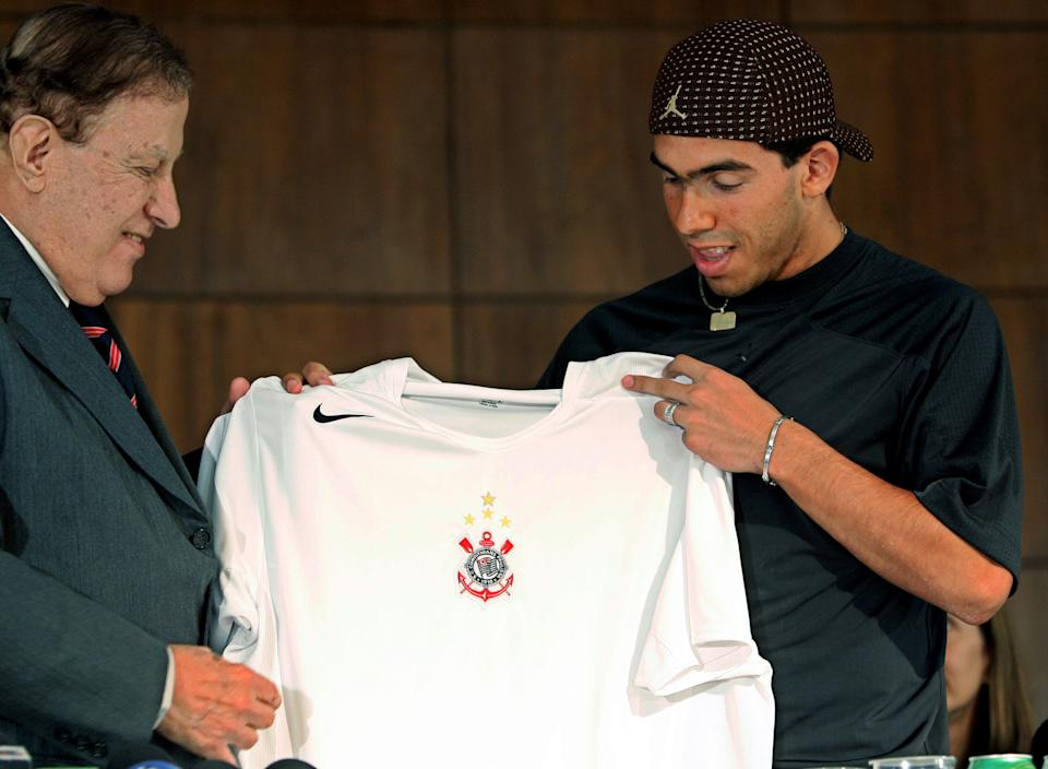 Argentine and former Boca Juniors soccer player Carlos Tevez, right, looks at the jersey of the Brazilian team Corinthians as he poses for photographs next to its president, Alberto Dualib, left, in Sao Paulo, Thursday, Jan. 13, 2005. (AP Photo/Victor R. Caivano) **EFE OUT**