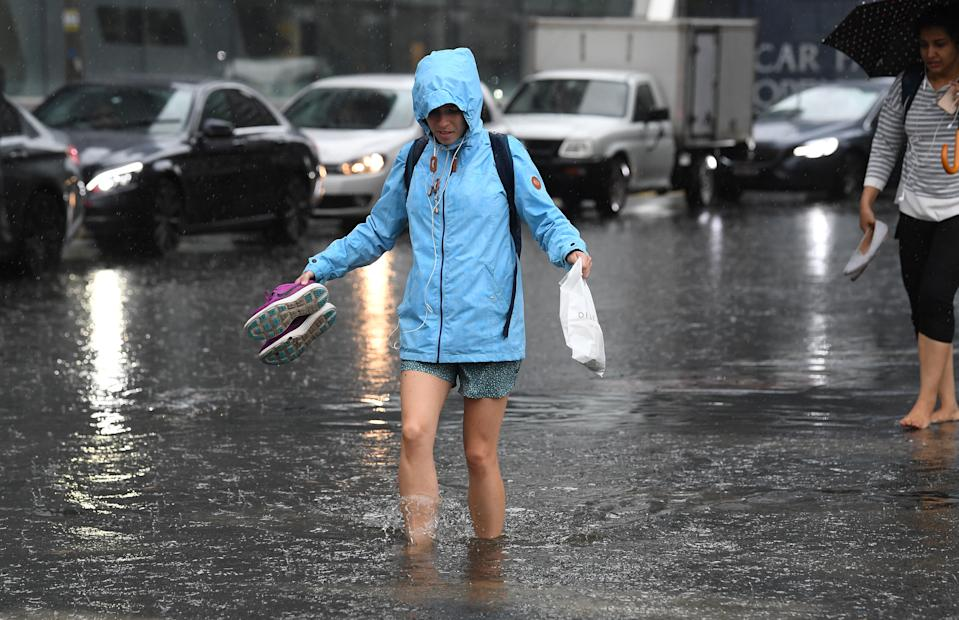 Pedestrians walk through flood waters at the corner of Clarendon and Cecil Street in South Melbourne, in 2018. Source: Julian Smith