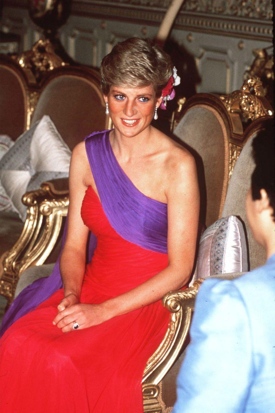 <p>In a red-and-purple chiffon dress by Catherine Walker at a dinner in Bangkok, Thailand. </p>