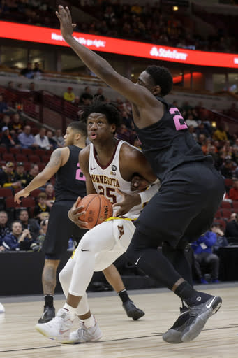 Minnesota's Eric Curry (24) drives against Penn State's Mike Watkins (24) during the first half of an NCAA college basketball game in the second round of the Big Ten Conference tournament, Thursday, March 14, 2019, in Chicago. (AP Photo/Kiichiro Sato)