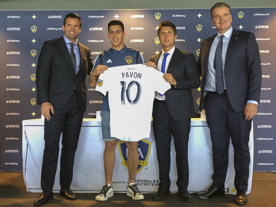 Forward Cristian Pavn, second from left, of Argentina, holds up his new LA Galaxy jersey at Dignity Health Sports Park in Carson, Calif., Thursday, Aug. 8, 2019. Standing alongside Pavon, Galaxy President Chris Klein, left, head coach Guillermo Barros Schelotto, second from right, and general manager Dennis te Kloese. The LA Galaxy acquired Pavn on loan from Argentina's Boca Juniors this week in one of the biggest player acquisitions in recent Major League Soccer history. (AP Photo/Greg Beacham)
