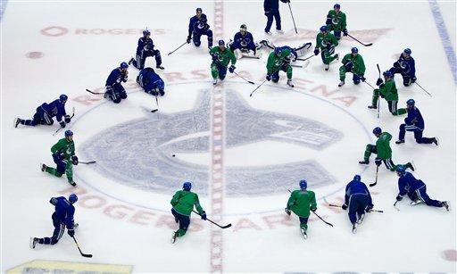 Vancouver Canucks players gather to stretch at the end of hockey practice in Vancouver, British Columbia on Tuesday April 10, 2012. The Vancouver Canucks and Los Angeles Kings are scheduled to play game 1 of an NHL Western Conference quarterfinal series Wednesday. (AP Photo/The Canadian Press, Darryl Dyck)