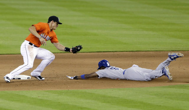 Miami Marlins second baseman Derek Dietrich, left, prepares to tag out Los Angeles Dodgers' Dee Gordon who was attempting to steal second in the fifth inning of a baseball game on Sunday, May 4, 2014, in Miami. (AP Photo/Wilfredo Lee)