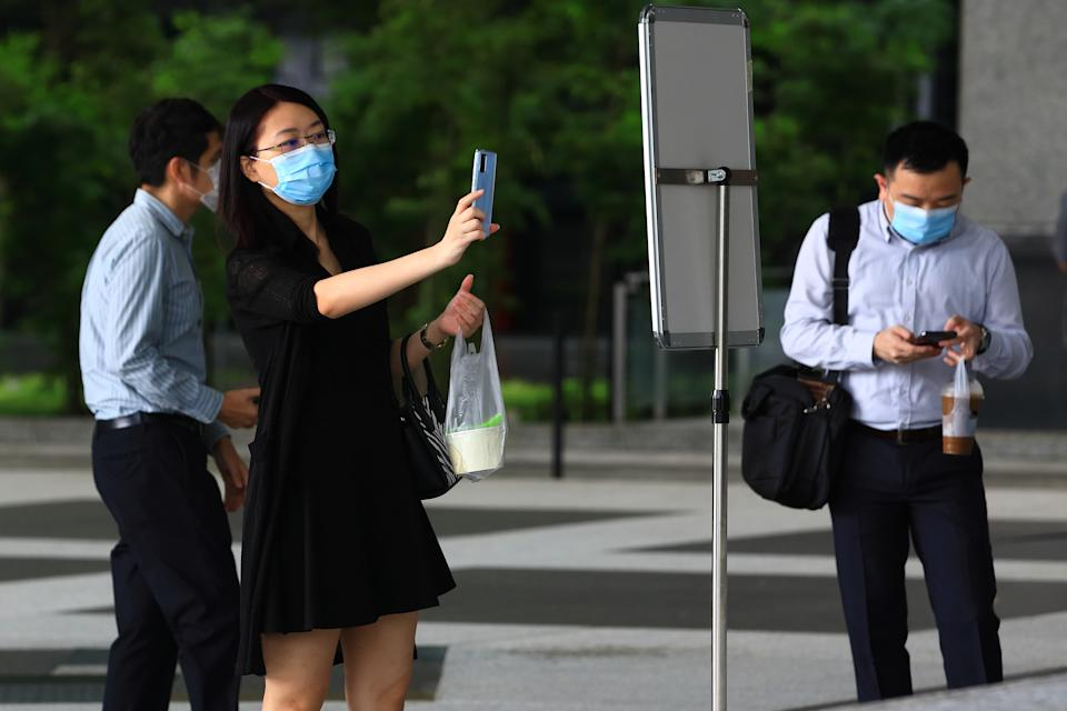 SINGAPORE - JUNE 12: A woman wearing protective masks scans a Safe Entry QR code before entering a bank on June 12, 2020 in Singapore. From June 2, Singapore embarked on phase one of a three phase approach against the coronavirus (COVID-19) pandemic as it began to ease the partial lockdown measures by allowing the safe re-opening of economic activities which do not pose high risk of transmission. This include the resumption of selected health services, re-opening of schools with school children attending schools on rotational basis, manufacturing and production facilities, construction sites that adhere to safety measures, finance and information services that do not require interactions and places of worship, amongst others. Retail outlets, social and entertainment activities will remain closed and dining in at food and beverage outlets will still be disallowed. The government will decide further to ease restriction by the middle of June if the infection rate within the community remains low.  (Photo by Suhaimi Abdullah/Getty Images)