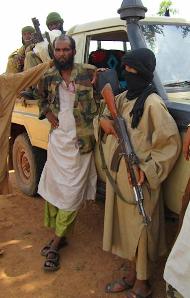 In this Thursday, Sept. 27, 2012 photo, 13-year-old fighter Abdullahi, right, holds an AK-47 as his Islamist commanders look on, in Douentza, Mali. Islamists in northern Mali have recruited and paid for as many as 1,000 children from rural towns and villages devastated by poverty and hunger. The Associated Press spoke with four children and conducted several dozen interviews with residents and human rights officials. The interviews provide evidence that a new generation in what was long a moderate and stable Muslim nation is becoming radicalized, as the Islamists gather forces to fight a potential military intervention backed by the United Nations. (AP Photo/Baba Ahmed)