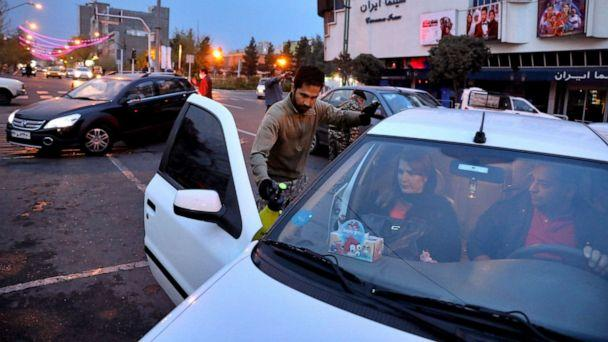 PHOTO: Iranian Revolutionary Guard and paramilitary Basij force members disinfect cars to help prevent the spread of the new coronavirus in downtown Tehran, Iran, March 25, 2020. (Ebrahim Noroozi/AP)