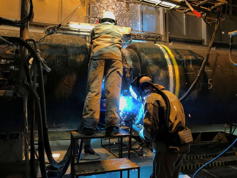 FILE PHOTO: Specialists work onboard Allseas' deep sea pipe laying ship Solitaire to prepare pipe for Nord Stream 2 pipeline in the Baltic Sea