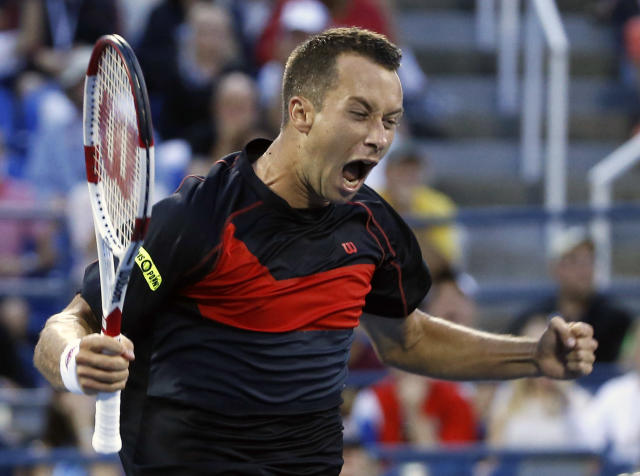 Philipp Kohlschreiber, of Germany, celebrates his upset victory over John Isner, of the United States, at the U.S. Open tennis tournament, Saturday, Aug. 30, 2014, in New York. Kohlschreiber won 7-6 (4), 4-6, 7-6 (2), 7-6 (4). (AP Photo/Elise Amendola)