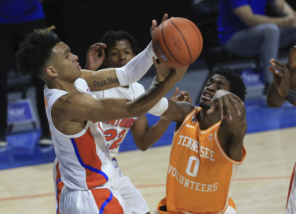 Florida guard Tre Mann (1) and Tennessee guard Davonte Gaines (0) compete for a rebound during the first half of an NCAA college basketball game Tuesday, Jan. 19. 2021, in Gainesville, Fla. (AP Photo/Matt Stamey)