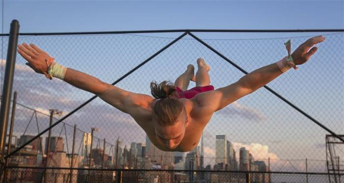 Greg Cooper spreads his arms as he works out on a trampoline at Trapeze School New York July 1, 2012.