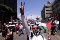 A demonstrator holding the flag of Palestine and showing a peace sign marches with others to the Israeli Consulate during a protest against Israel and in support of Palestinians during the current conflict in the Middle East, Saturday, May 15, 2021, in the Westwood section of Los Angeles. (AP Photo/Ringo H.W. Chiu)