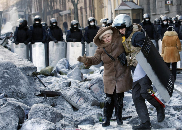 A protester wearing improvised protective gear helps a woman cross near the barricade in front of riot police in Kiev, Ukraine, Friday Jan. 24, 2014. Protesters have seized a government building in the Ukrainian capital while also maintaining the siege of several governors' offices in the country's west, raising the pressure on the government. After meeting with President Viktor Yanukovych on Thursday, opposition leaders told the crowds that he has promised to ensure the release of dozens of protesters detained after clashes with police and stop further detentions. (AP Photo/Darko Vojinovic)