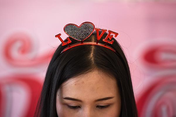 """A district office worker wears a Valentine's Day-themed headband as she prepares marriage documents for couples at the central post office in Bang Rak, or """"Love Village"""", district in Bangkok on February 14, 2017."""