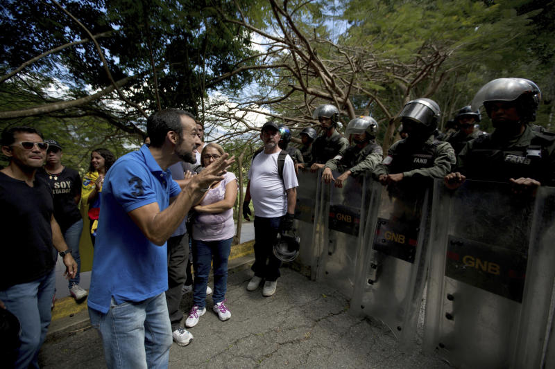 A Relative of Abraham Agostini argues with a line of Venezuelan Bolivarian national Guards blocking his way to the main entrance at the cemetery in Caracas Venezuela, Saturday, Jan. 20, 2018. Jose Diaz Pimentel and Abraham Agostini, members of the rebel group led by Venezuelan former police Oscar Perez, who died at the beginning of the week in an operation of the security forces, were buried in a controlled manner by the authorities and between protests of their Relatives, who were prevented from accessing the cemetery. (AP Photo/Fernando Llano)