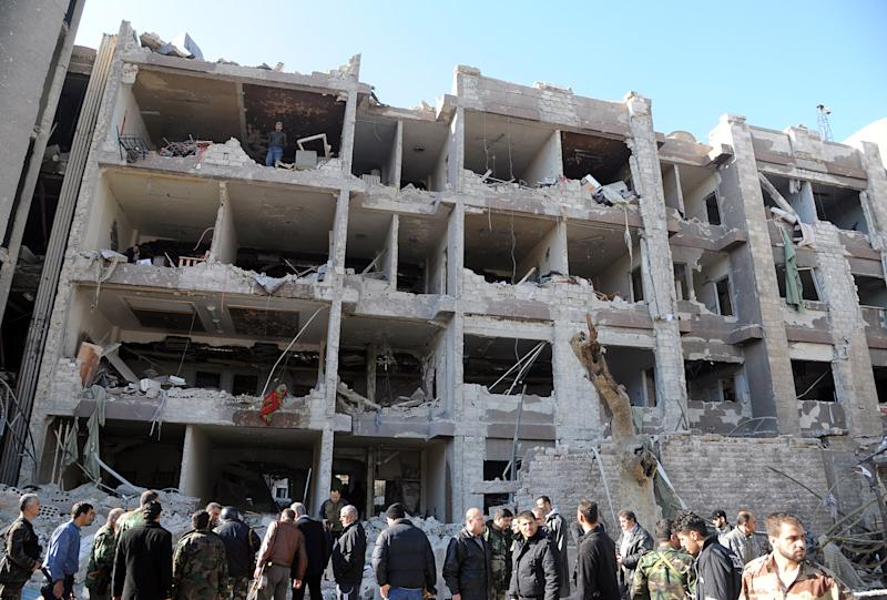 "In this photo released by the Syrian official news agency SANA, Syrian security officers investigate a damaged building of the air intelligence forces, which was attacked by one of two explosions, in Damascus, Syria, on Saturday, March 17, 2012. Two ""terrorist explosions"" struck security targets in the Syrian capital Saturday morning, killing a number of civilians and security forces, the country's state news agency said. The report said preliminary reports indicated they blasts were caused by car bombs that hit the aviation intelligence department and the criminal security department. (AP Photo/SANA)"