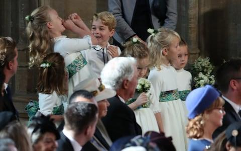 Prince George is pictured playing with one of the bridesmaids as they wait for the ceremony to begin - Credit: PA