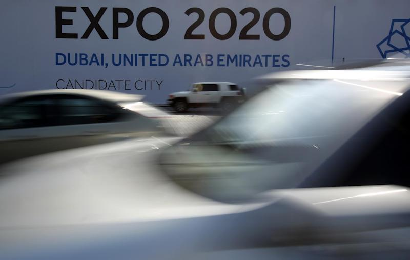 In this Wednesday Nov. 20, 2013, vehicles pass by a billboard advertising Dubai as a candidate city for the Expo 2020 in Dubai, United Arab Emirates. The logo for Dubai's bid to host the Expo 2020 reflects a push by the city's leaders to avert another financial crisis like the one that brought the city to its knees in 2008. Dubai saw property values slashed by more than half and the city's government needed a $10 billion bailout from oil-rich neighbor Abu Dhabi in 2009. (AP Photo/Kamran Jebreili)