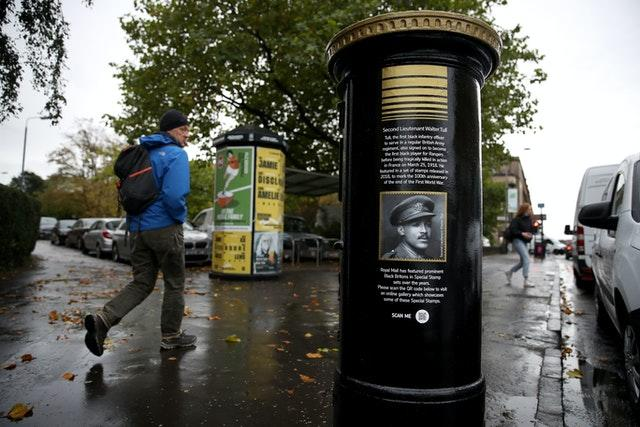 Members of the public walk past a black postbox featuring an image of Second Lieutenant Walter Tull, on Byres Road, Glasgow, one of four special edition postboxes unveiled by Royal Mail to mark Black History Month