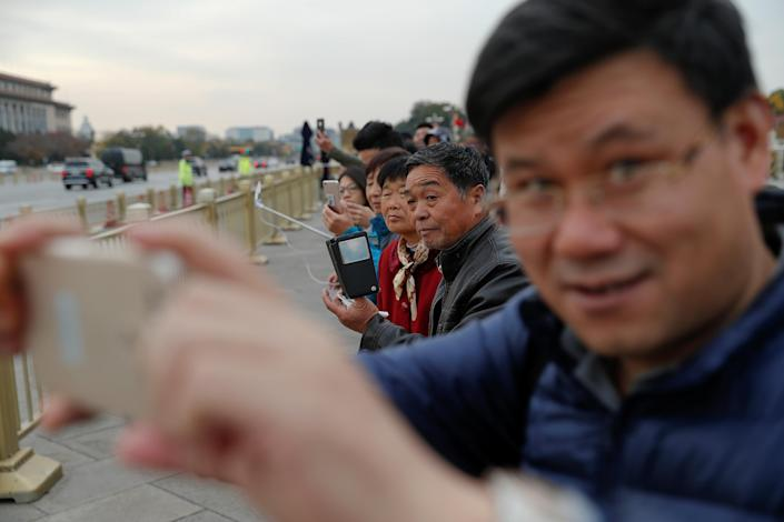 <p>People try to get a glimpse of President Donald Trump as his motorcade passes by Tiananmen square in Beijing, China, Nov. 8, 2017. (Photo: Damir Sagolj/Reuters) </p>