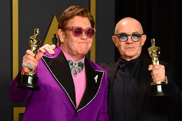"""Singer-songwriter Elton John and lyricist Bernie Taupin pose in the press room with the Oscar for Best Original Song for """"(I'm Gonna) Love Me Again"""" from the movie """"Rocketman"""" during the 92nd Oscars at the Dolby Theater in Hollywood, California on February 9, 2020. (Photo by FREDERIC J. BROWN/AFP via Getty Images)"""
