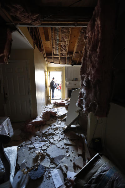 Houston Fire Chief Samuel Peña talks with Hortensia Lima, whose home was seriously damaged and deemed uninhabitable on Stanford Court in Houston, Sunday, Jan. 26, 2020, after the Friday morning explosion at the Watson Grinding Manufacturing plant.  (Karen Warren/Houston Chronicle via AP)