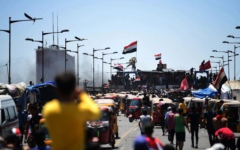 Protesters carry the Iraqi national flag as they gather on the Al-Jumhuriya bridge, which leads to the headquarters of the Iraqi government inside the high security Green Zone area - Shutterstock