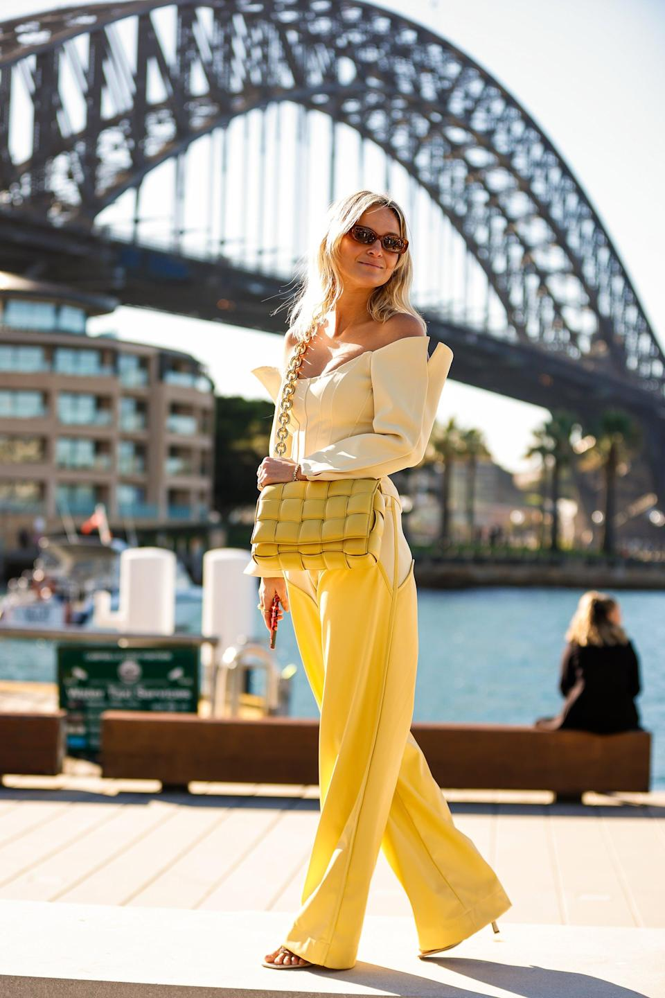 """<a href=""""https://repeller.com/the-best-winter-style-hack-involves-dressing-like-butter/"""" rel=""""nofollow noopener"""" target=""""_blank"""" data-ylk=""""slk:Stick-of-butter fashion"""" class=""""link rapid-noclick-resp"""">Stick-of-butter fashion</a> took the streets of Sydney by storm. <br><br><em><a href=""""https://www.instagram.com/nadiafairfax/?hl=en"""" rel=""""nofollow noopener"""" target=""""_blank"""" data-ylk=""""slk:Nadia Fairfax"""" class=""""link rapid-noclick-resp"""">Nadia Fairfax</a> wearing a <a href=""""https://shop.parisgeorgiastore.com/products/03-henry-top-daffy-cream?variant=39318430187714"""" rel=""""nofollow noopener"""" target=""""_blank"""" data-ylk=""""slk:Paris Georgia top"""" class=""""link rapid-noclick-resp"""">Paris Georgia top</a>, <a href=""""https://shop.parisgeorgiastore.com/products/03-oversized-cowboy-trousers?variant=39318954606786"""" rel=""""nofollow noopener"""" target=""""_blank"""" data-ylk=""""slk:Paris Georgia pants"""" class=""""link rapid-noclick-resp"""">Paris Georgia pants</a>, a <a href=""""https://www.fwrd.com/product-bottega-veneta-the-chain-cassette-in-butter-gold/BOTT-WY464/"""" rel=""""nofollow noopener"""" target=""""_blank"""" data-ylk=""""slk:Bottega Veneta bag,"""" class=""""link rapid-noclick-resp"""">Bottega Veneta bag,</a> and <a href=""""https://www.banbeeyewear.com/collections/new-arrivals/products/the-bella-honey-tort-brown"""" rel=""""nofollow noopener"""" target=""""_blank"""" data-ylk=""""slk:Banbé sunglasses"""" class=""""link rapid-noclick-resp"""">Banbé sunglasses</a>. </em><span class=""""copyright"""">Photo: Hanna Lassen/Getty Images.</span>"""