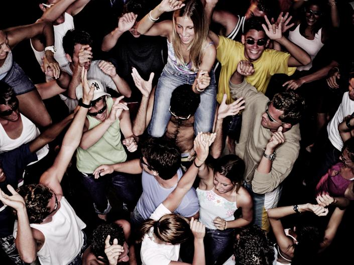 A crowd of people parties in a nightclub