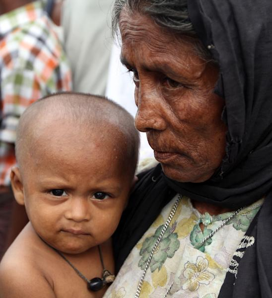 In this photo taken on Sept. 8, 2012, a Muslim woman holds an infant at a refugee camp in Sittwe, Rakhine State, western Myanmar. Three-and-a-half months after some of the bloodiest clashes in a generation between Myanmar's ethnic Rakhine Buddhists and stateless Muslims known as Rohingya left the western town of Sittwe in flames, nobody is quite sure when -or even if- the Rohingya will be allowed to resume the lives they once lived here. (AP Photo/Khin Maung Win)