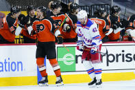 Philadelphia Flyers' Kevin Hayes, left, celebrates with teammates past New York Rangers' Brendan Smith after scoring a goal during the second period of an NHL hockey game, Wednesday, Feb. 24, 2021, in Philadelphia. (AP Photo/Matt Slocum)