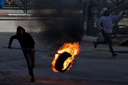 A Palestinian protester moves a burning tire during clashes with Israeli troops in Hebron, in the occupied West Bank March 29, 2019. REUTERS/Mussa Qawasma