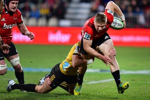 The Canterbury Crusaders' Jack Goodhue (R) is tackled by the Wellington Hurricanes' Ricky Riccitelli during their Super Rugby semi-final match, at the AMI Stadium in Christchurch, on July 28, 2018