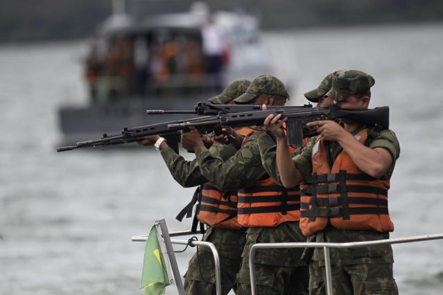 """Navy soldiers take aim during simulation exercise Operation """"Amazonia Azul"""" (Blue Amazon), against the invasion of protected areas in Brasilia February 20, 2014. The operation aims to combat illegal activities on Brazilian waters and prepare Brazil's Navy for the 2014 World Cup, according to the Brazil's Naval operations command. REUTERS/Ueslei Marcelino (BRAZIL - Tags: MILITARY)"""