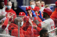 Philadelphia Phillies' Odubel Herrera is greeted at the dugout by teammates after hitting a three-run home run in the first inning of a baseball game against the Atlanta Braves, Friday, May 7, 2021, in Atlanta. (AP Photo/John Bazemore)