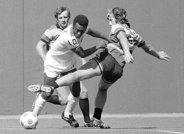 FILE - In this May 15 1977, file photo, New York Cosmos' Pele (10) dribbles the ball between Fort Lauderdale Strikers' Bobby Bell, right, and Ray Lugg during NASL soccer game at Giants Stadium in East Rutherford, N.J. Pele will watching, not playing, when two franchises that helped get soccer rolling in this country renew acquaintances. The Brazilian great's former team, the Cosmos, visit the Strikers on Saturday, rekindling memories of how more than 70,000 fans used to see them play. (AP Photo/File)